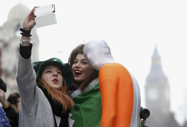 Alexandra Bonderenko (L) and her sister Lena Bonderenko from Moscow have their picture taken with  a participant of the St Patrick's Day parade, central London, March 15, 2015. (Photo by Paul Hackett/Reuters)