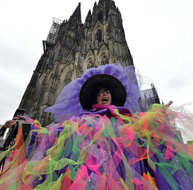 A female reveller celebrates in front of the cathedral during the start of the street carnival in Cologne, Germany, on Thursday, February 4, 2016. (Photo by Martin Meissner/AP Photo)