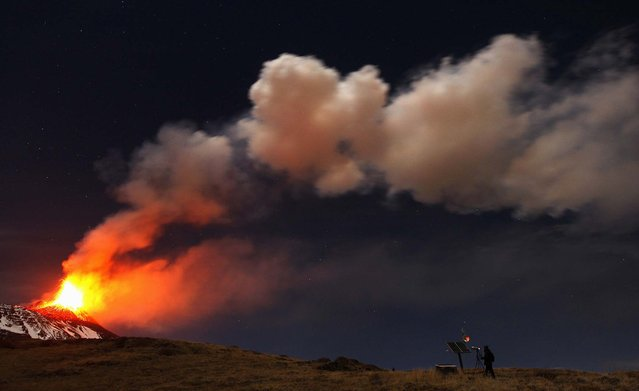 A photographer takes pictures of Mount Etna spewing lava as it erupts on November 17, 2013. (Photo by Antonio Parrinello/Reuters)