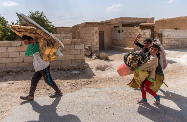Residents gesture while carrying their belongings as they head back to their homes after Kurdish People's Protection Units (YPG) said they took control of Abd al-Aziz mountain, Hasaka province May 20, 2015. (Photo by Rodi Said/Reuters)