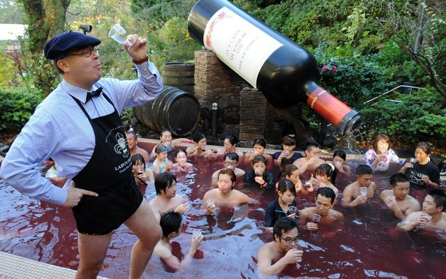 Bourgogne wine maker Laboure-Roi vice president Thibault Garin (L) toasts the company's 2013 Beaujolais Nouveau wine with guests in the wine spa at the Hakone Yunessun spa resort facilities in Hakone town, Kanagawa prefecture, some 100-kilometre west of Tokyo on November 21, 2013. As the new vintage Beaujolais Nouveau is officially uncorked, Hakone Yunessun started the annual 10-day-long Beaujolais Nouveau spa event with a guest of the wine maker's executive. (Photo by Toshifumi Kitamura/AFP Photo)