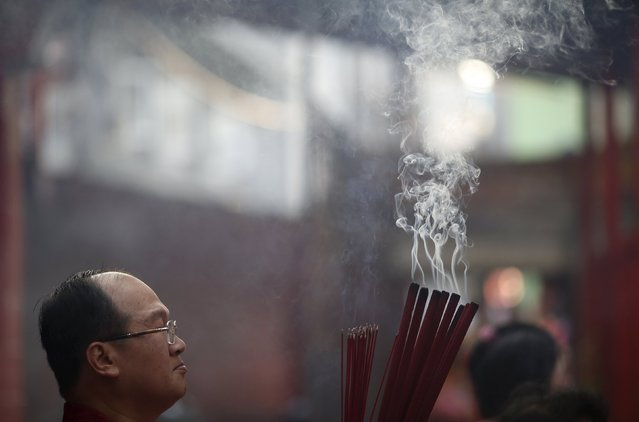 A man waits to plant joss sticks at Dharma Bhakti Temple on the first day of the  Lunar New Year in Jakarta, Indonesia February 8, 2016. (Photo by Darren Whiteside/Reuters)