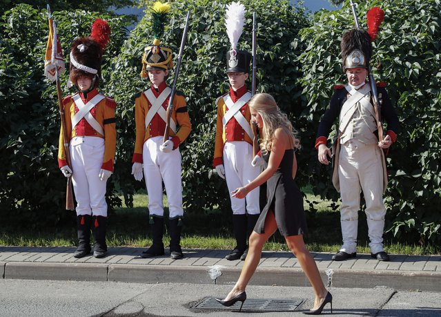 A woman passes Members of historical clubs dressed in the uniform of French soldiers during ceremony of repatriation of the remains of French General Charles-Etienne Gudin de la Sablonniere, participant in the French Revolutionary wars and Napoleonic wars, to France in Moscow airport Vnukovo-3, Russia, 13 July 2021. One of Napoleon Bonaparte's favourite military commanders died in the Battle of Smolensk during the Russian campaign of 1812. The search for his remains was one of the main goals of the joint archaeological expedition, which the historians of the two countries, led by Pierre Malinowski, President of the Foundation for the Development of Russian- French Historical Initiatives, began in the summer of 2019. A significant find was made during excavations at the Royal Bastion in the Lopatinsky Garden of Smolensk. (Photo by Sergei Ilnitsky/EPA/EFE)