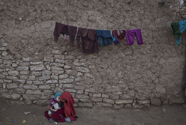 An Afghan refugee girl tends to her brother while sitting on the ground in front of their mud home in a slum on the outskirts of Islamabad, Pakistan, Sunday, February 22, 2015. (Photo by Muhammed Muheisen/AP Photo)