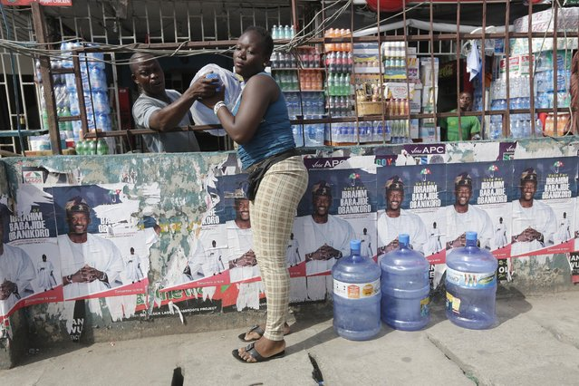 A vendor sells bottle water near election campaign posters on the street  in Lagos, Nigeria, Friday, April 10, 2015. Nigeria goes to the polls Saturday to elect governors and state Assembly. (Photo by Sunday Alamba/AP Photo)