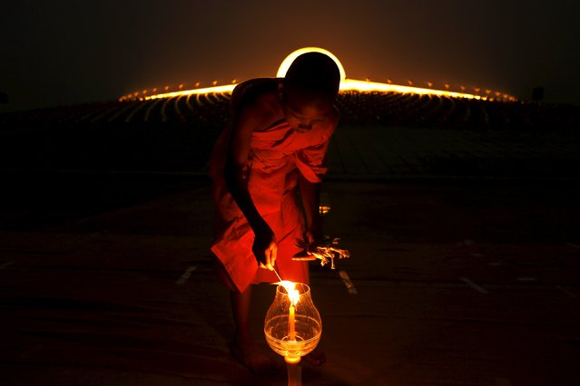 A Buddhist monk lights a candle at Wat Phra Dhammakaya during a ceremony on Makha Bucha Day in Pathum Thani province, north of Bangkok February 22, 2016. (Photo by Jorge Silva/Reuters)
