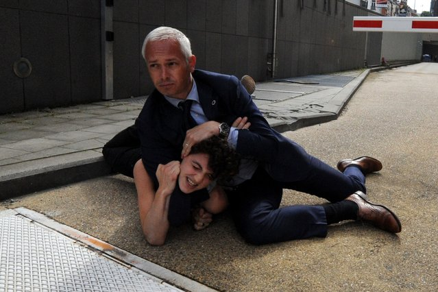 Activist Margo Frutier from the women's rights group FEMEN is detained by a security personnel after staging a protest near the European Commission during a visit by Tunisia's Prime Minister Ali Larayedh in Brussels, June 25, 2013. (Photo by Laurent Dubrule/Reuters)