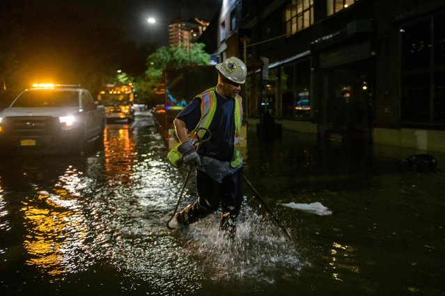 A worker unblocks drains on a street affected by floodwater in Brooklyn, New York early on September 2, 2021, as flash flooding and record-breaking rainfall brought by the remnants of Storm Ida swept through the area. (Photo by Ed Jones/AFP Photo)