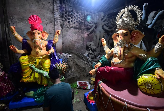 An artist gives finishing touches to an idol of the elephant-headed Hindu God Ganesha at a workshop ahead of the Ganesh Chaturthi festival in Allahabad on September 7, 2021. (Photo by Sanjay Kanojia/AFP Photo)