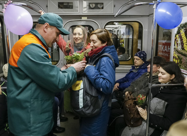 Kiev's subway staff offers flowers to female passengers ahead of the International Women's Day in Kiev, Ukraine, March 2, 2016. (Photo by Gleb Garanich/Reuters)