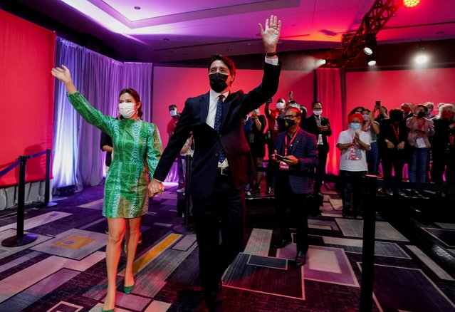 Canada's Liberal Prime Minister Justin Trudeau and his wife Sophie Gregoire wave to supporters during the Liberal election night party in Montreal, Quebec, Canada, September 21, 2021. (Photo by Carlos Osorio/Reuters)