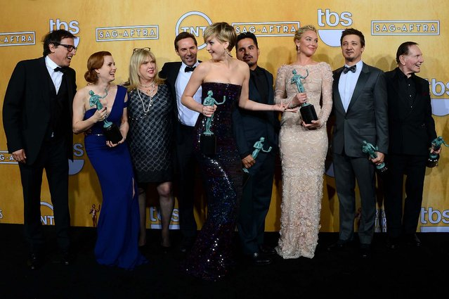 """(L-R) Writer-director David O. Russell, actors Amy Adams, Colleen Camp, Alessandro Nivola, Jennifer Lawrence, Michael Pena, Elisabeth Rohm, Jeremy Renner, and Paul Herman, winners of the Outstanding Performance by a Cast in a Motion Picture award for """"American Hustle"""", pose in the press room. (Photo by Ethan Miller/Getty Images)"""