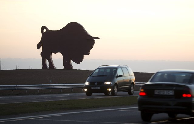 Cars drive past a giant metal statue of a bison in a field near the village of Dudichi, southwest of Minsk, April 24, 2015. European bison, a national symbol of Belarus, is the largest wild animal in the country. (Photo by Vasily Fedosenko/Reuters)