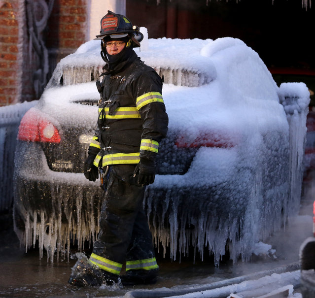 A North Hudson County Fire Department firefighter walks in front of an iced covered vehicle near a building where a a six-alarm fire was put out by officials, Friday, January 24, 2014, in Union City, N.J. The fire began in one residential apartment building on 19th Street around 11:30 p.m. Thursday and quickly spread to two adjacent buildings. (Photo by Julio Cortez/AP Photo)
