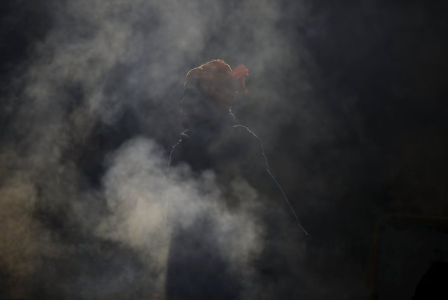 Smoke rises as a Hindu holy man, or sadhu, stands near the fire during the Shivaratri festival at the premises of Pashupatinath Temple in Kathmandu, Nepal, March 7, 2016. (Photo by Navesh Chitrakar/Reuters)