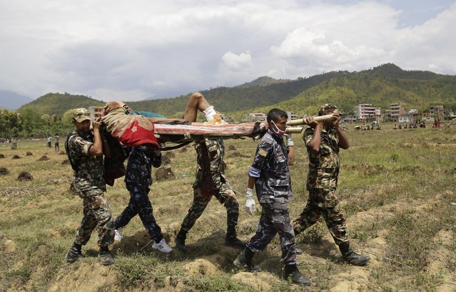 Nepalese rescuers carry a wounded man on a makeshift stretcher to a waiting Indian air force helicopter as they evacuate victims of Saturday's earthquake from Trishuli Bazar to Kathmandu airport in Nepal, Monday, April 27, 2015. (Photo by Altaf Qadri/AP Photo)