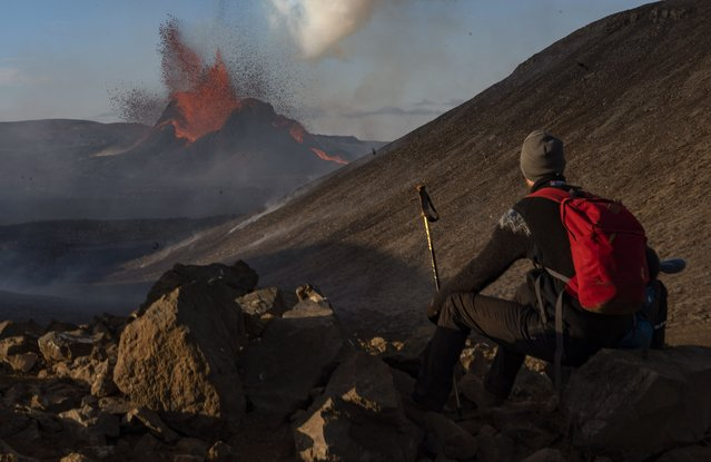 A man watches as lava spews from an eruption of the Fagradalsfjall volcano on the Reykjanes Peninsula in southwestern Iceland on Tuesday, May 11, 2021. (Photo by Miguel Morenatti/AP Photo)