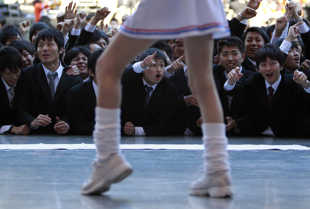 Japanese college students look at cheerleaders during a job-hunting rally in Tokyo January 29, 2014. According to the rally organizers, about 1,500 students from vocational schools attend the rally to boost their morale ahead of their job hunt. (Photo by Yuya Shino/Reuters)