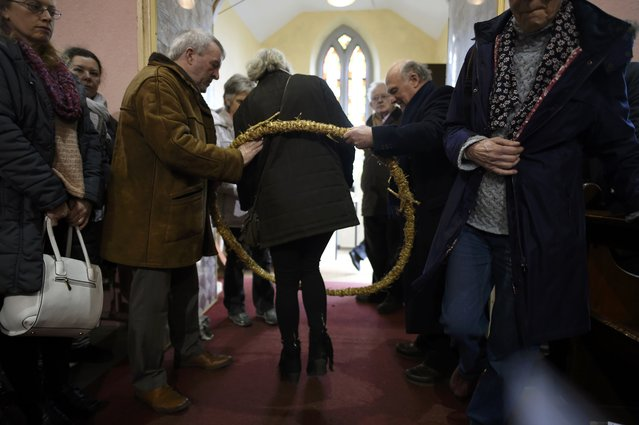 People leave mass through a St. Brigid's girdle which blesses them after a Pattern Day mass to St. Brigid beside the holy well of St. Brigid in Liscannor, Ireland February 1, 2017. (Photo by Clodagh Kilcoyne/Reuters)