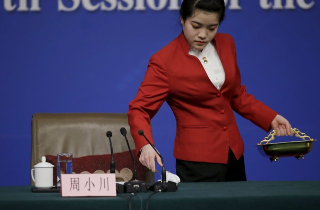 A tea attendant serves ahead of a news conference by Zhou Xiaochuan, Governor of the People's Bank of China, on the sidelines of the National People's Congress (NPC), China's parliament, in Beijing, China, March 12, 2016. (Photo by Jason Lee/Reuters)