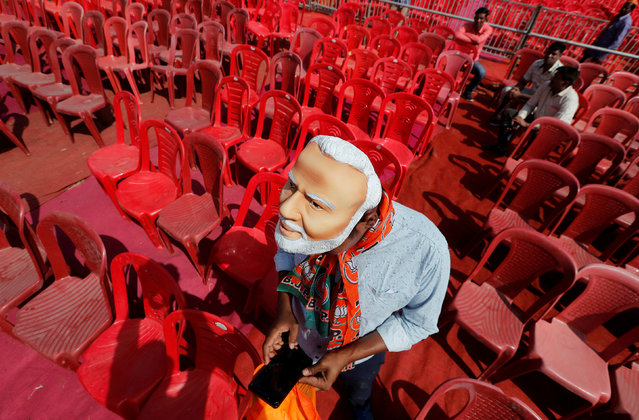 A supporter of India's ruling Bharatiya Janata Party (BJP) wearing a mask of Prime Minister Narendra Modi checks his mobile phone as he attends an election campaign rally being addressed by Modi in Meerut in the northern Indian state of Uttar Pradesh, India, March 28, 2019. (Photo by Adnan Abidi/Reuters)