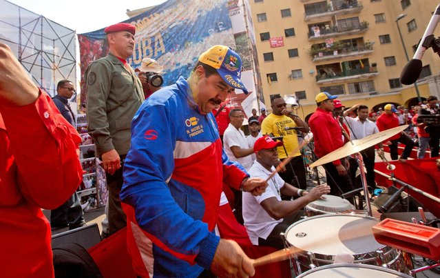 Venezuela's President Nicolas Maduro plays the drums as he arrives for a May Day rally in Caracas, Venezuela, Friday, May 1, 2015. (Photo by Fernando Llano/AP Photo)