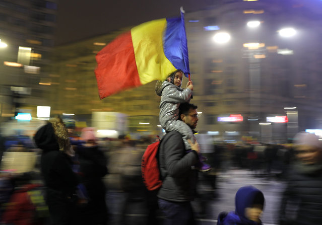 Young kid carries Romanian national flag during a demonstration in Bucharest, Romania, Sunday, February 5, 2017. Romania's government met Sunday to repeal an emergency decree that decriminalizes official misconduct, a law that has prompted massive protests at home and widespread condemnation from abroad. (Photo by Vadim Ghirda/AP Photo)