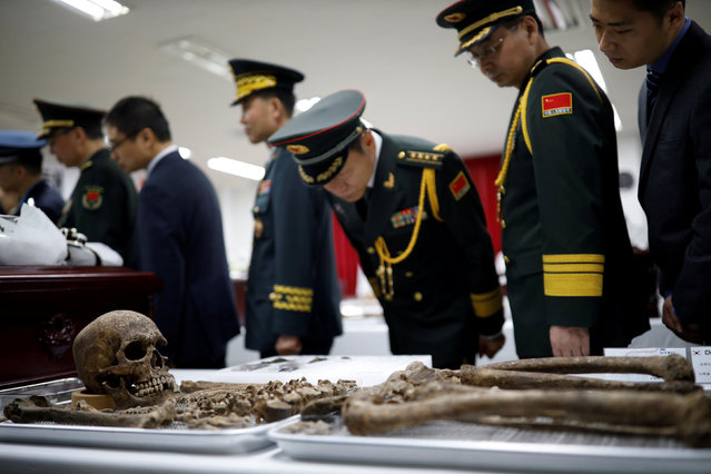 Chinese military officials look at the remains of a Chinese soldier who fought in the Korean War, during the coffin rites in Incheon, South Korea, April 1, 2019. (Photo by Kim Hong-Ji/Reuters/Pool)