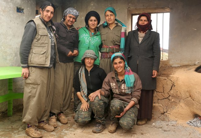 Female Kurdistan Workers Party (PKK) fighters pose for a group picture, with a displaced Yazidi woman (R) who lives near the base in Sinjar, March 13, 2015. (Photo by Asmaa Waguih/Reuters)