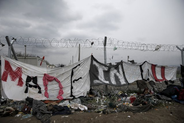 """A handmade banner hangs at the border fence at the Greek-Macedonian border, at a makeshift camp for refugees and migrants near the village of Idomeni, Greece March 16, 2016. Banner reads, """"Made in EU"""". (Photo by Alkis Konstantinidis/Reuters)"""