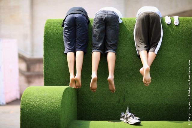 Young boys lean over a giant sofa on the South Bank