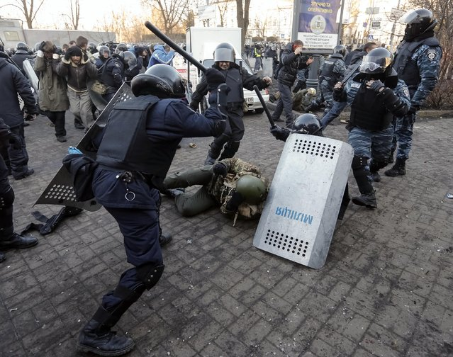 Riot police beat an anti-government protester during clashes in Kiev February 18, 2014. Ukrainian riot police charged protesters occupying a central Kiev square early on Wednesday after the bloodiest day since the former Soviet republic, caught in a geopolitical struggle between Russia and the West, won its independence. (Photo by Reuters/Stringer)