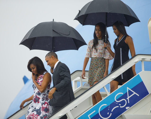 President Barack Obama, second from left, arrives with first lady Michelle Obama, left, and their daughters Sasha, right, and Malia, as they exit Air Force One at the airport in Havana, Cuba, Sunday, March 20, 2016. Obama and his family are traveling to Cuba, the first U.S. president to visit the island in nearly 90 years. (Photo by Pablo Martinez Monsivais/AP Photo)