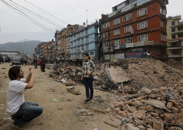 A tourist gets her picture clicked in front of a collapsed house, after the Saturday's earthquake, in Kathmandu, May 2, 2015. (Photo by Adnan Abidi/Reuters)