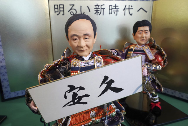 """In this Thursday, March 28, 2019, photo, Japanese traditional dolls depicting Japanese Chief Cabinet Secretary Yoshihide Suga holding the new era name """"Ankyu"""", speculated by about 180 general public, displayed with a doll depicting Japanese Prime Minister Shinzo Abe, right, at Kyugetsu, a Japanese traditional doll company, in Tokyo. What's in a name? Quite a lot if you're a Japanese citizen awaiting the official announcement Monday, April 1, 2019 of what the soon-to-be-installed new emperor's next era will be called. It's a proclamation that has happened only twice in nearly a century, and the new name will follow Emperor Naruhito, after his May 1 investiture, for the duration of his rule, attaching itself to much of what happens in Japan. (Photo by Eugene Hoshiko/AP Photo)"""