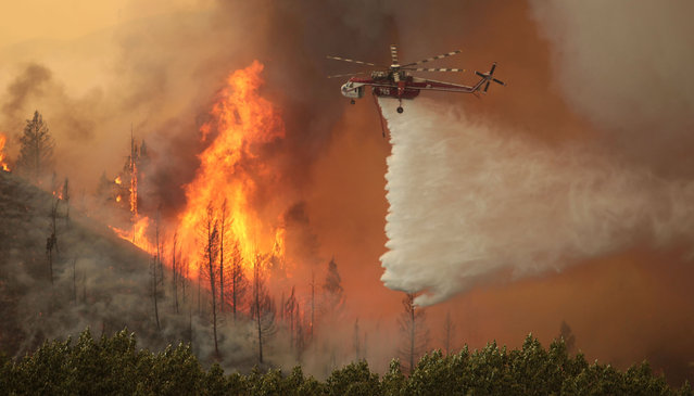 In this August 16, 2013, file photo a helicopter battles a Beaver Creek Fire north of Hailey, Idaho. (Photo by Ashley Smith/The Times-News via AP Photo)