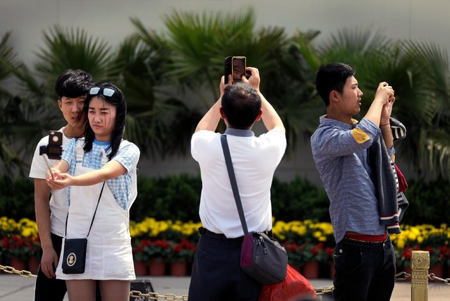 A couple uses a selfie stick to take a photo of themselves as visitors using smartphones take souvenir photos at Tiananmen Square in Beijing, China, Thursday, April 30, 2015. Selfie stick are gaining popularity in China, and many people are using them at popular tourist destinations. (Photo by Andy Wong/AP Photo)