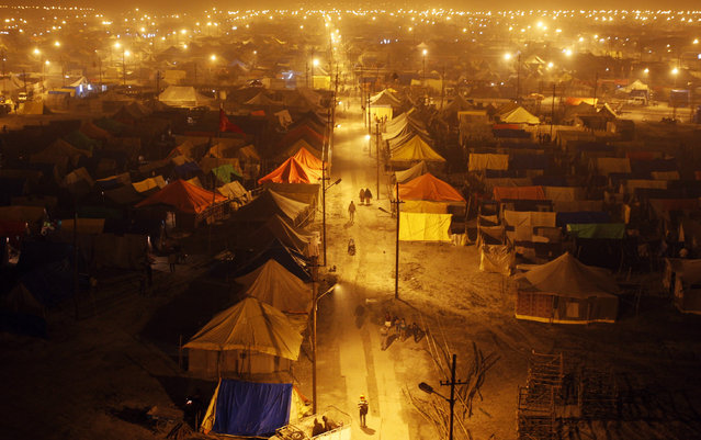 People walk past a tent city erected for masses of pilgrims on the banks of river Ganges on the occasion of the Makar Sankranti festival in Allahabad January 14, 2014. (Photo by Jitendra Prakash/Reuters)