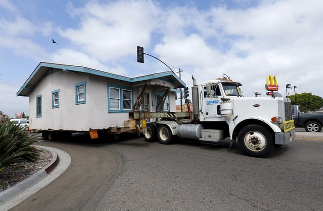 An old home is trucked away for recycling and resale after being removed from its neighborhood in San Diego, California March 28, 2016. (Photo by Mike Blake/Reuters)