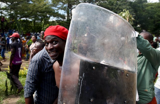 A man holds a riot police shield as he celebrates in Bujumbura, Burundi, May 13, 2015. Crowds poured onto the streets of Burundi's capital on Wednesday to celebrate after a general said he was dismissing President Pierre Nkurunziza for violating the constitution by seeking a third term in office, a Reuters witness said. (Photo by Goran Tomasevic/Reuters)