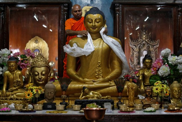 A Buddhist monk offers a khada, traditional ceremonial scarf, on a statue of Lord Buddha inside a temple ahead of the Buddha Purnima festival, also known as Vesak Day, in Kolkata, India May 17, 2019. (Photo by Rupak De Chowdhuri/Reuters)