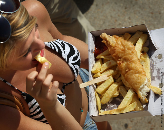 A s*xy woman eats fish and chips on the beach