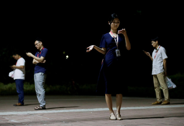 An employee learns to dance from an app as she waits for a taxi after work overtime at Huawei headquarters in Shenzhen, Guangdong province, China on May 29, 2019. (Photo by Jason Lee/Reuters)