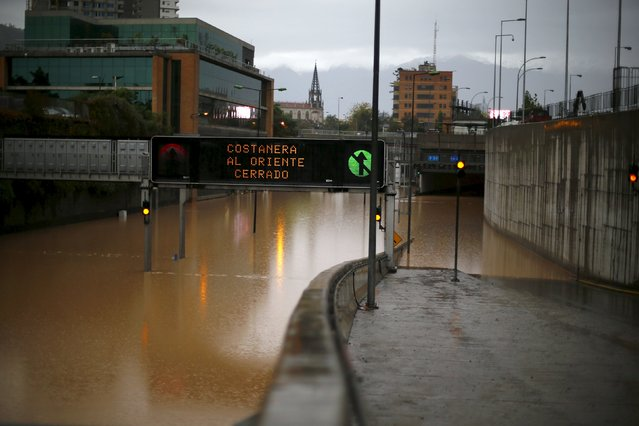 "A view of a flooded highway access in Santiago April 17, 2016. The sign reads ""Costanera highway closed to east"". (Photo by Ivan Alvarado/Reuters)"