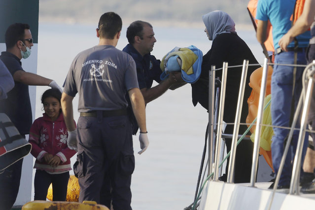 A mother gives her baby to a coast guard officer as she disembarks from a vessel at the port of Mitylene after being picked up by the Greek coast guard near the northeast Greek island of Lesvos on Wednesday, June 17, 2015. Around 100,000 migrants have entered Europe so far this year as Italy and Greece have borne the brunt of the surge with many more migrants expected to arrive from June through to September. (AP Photo/Thanassis Stavrakis)