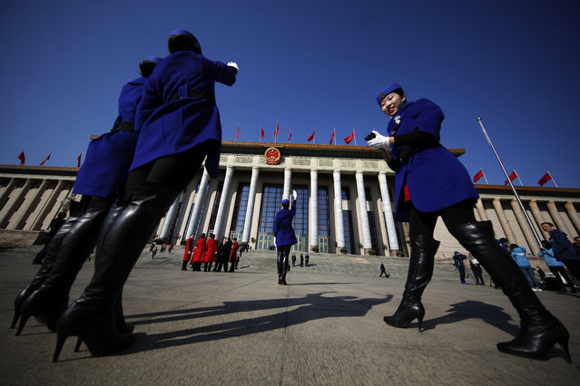 In this Sunday, March 5, 2017, photo, hospitality staff take souvenir photos in front of the Great Hall of the People where the National People's Congress is held in Beijing. (Photo by Andy Wong/AP Photo)