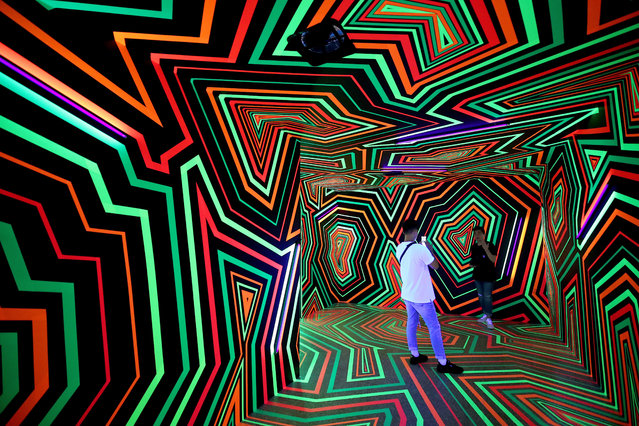 """People take souvenir photos inside the installation """"Fading colors and Glow"""" by the Berlin base art group """"Tape That"""" during an art exhibition in Taipei, Taiwan, 16 July 2019. The presentation of the art installations will run until 01 September 2019. (Photo by Ritchie B. Tongo/EPA/EFE)"""