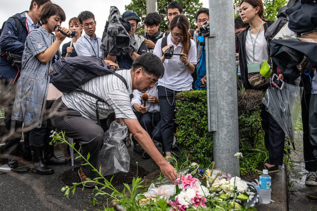 """A man is surrounded by members of the media as he lays flowers near the Kyoto Animation Co studio building following an arson attack on July 19, 2019 in Kyoto, Japan. Thirty three people are believed dead and dozens injured after a suspected arson attack on the animation studio. Police were quoted by local media as saying a 41 year-old man broke into the Kyoto Animation Co studio on Thursday morning and sprayed petrol before igniting it. Japan's Prime Minister Shinzo Abe described the incident as """"too appalling for words"""". (Photo by Carl Court/Getty Images)"""