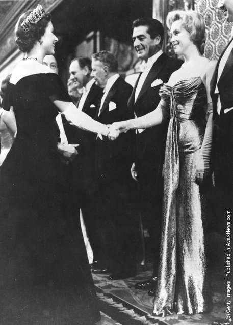 Queen Elizabeth II shaking hands with Marilyn Monroe (1926 - 1962) who stands next to Victor Mature (1913 - 1999) at a Royal Film Performance of 'The Battle of the River Plate' at the Empire Theatre, Leicester Square, London