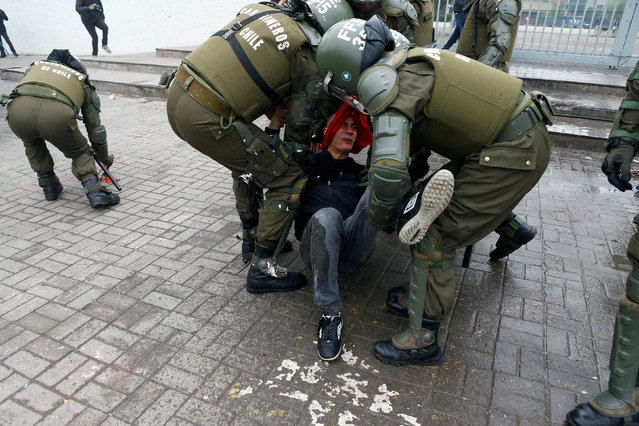 A demonstrator is detained during a rally commemorating May Day in Santiago, Chile May 1, 2016. (Photo by Ivan Alvarado/Reuters)